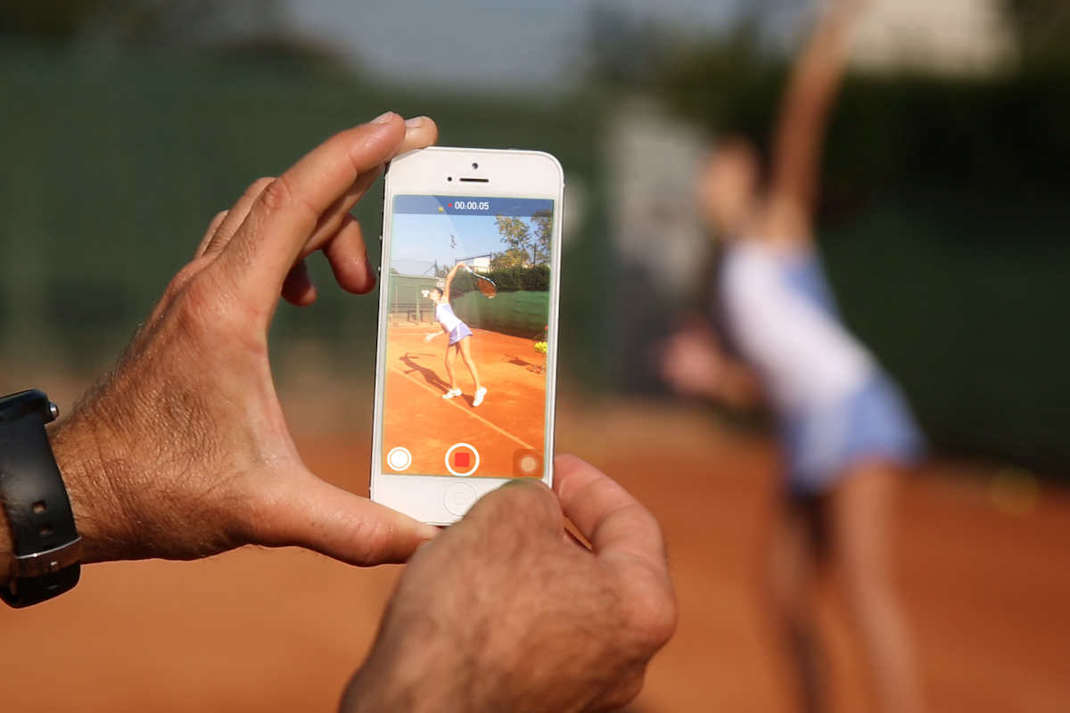 Tennis coach holding a smartphone and filming a female tennis player on a clay tennis court in Barcelona