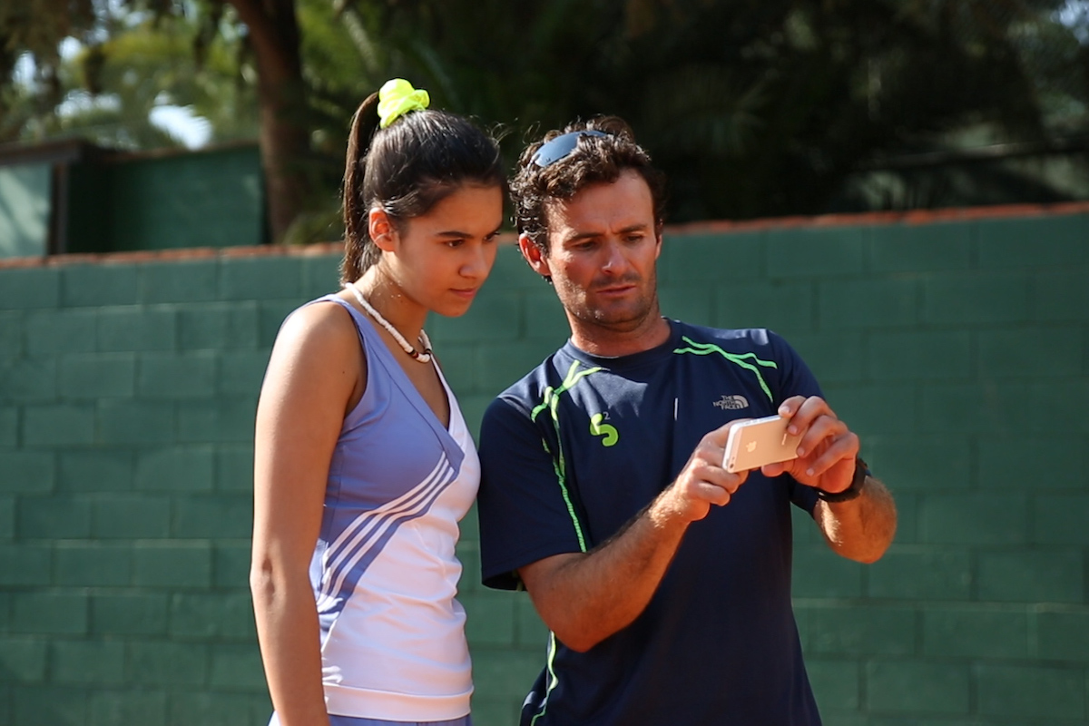 Tennis coach and a female tennis player looking at the smartphone and analysing tennis serve on a clay tennis court in Barcelona